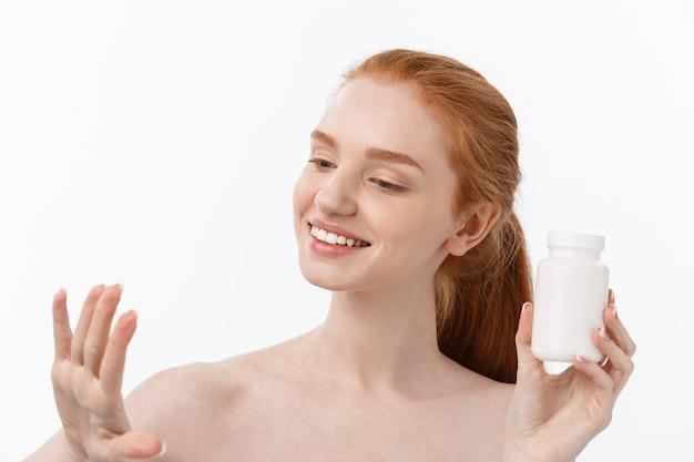 Porträt einer gut aussehenden jungen kaukasischen frau, die pillen hält und versucht, sich um das immunsystem und die gesundheit über grau zu kümmern