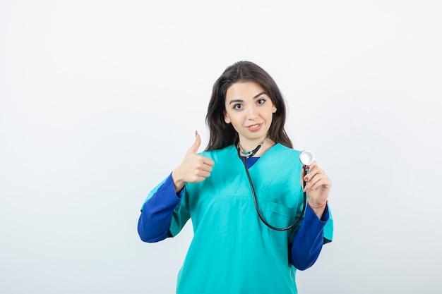 Porträt einer gut aussehenden jungen krankenschwester mit dem stethoskop, das sich daumen zeigt.