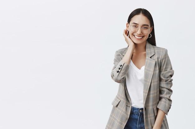 Porträt einer gut aussehenden stilvollen frau in brille und trendiger jacke, die den ohrring berührt, während sie über die graue wand flirtet