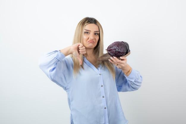Porträt einer gutaussehenden frau, die zwei purpurkohlgemüse hält