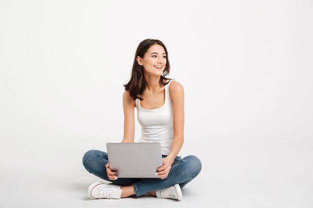 Porträt einer heitren frau kleidete im trägershirt an, das laptop hält