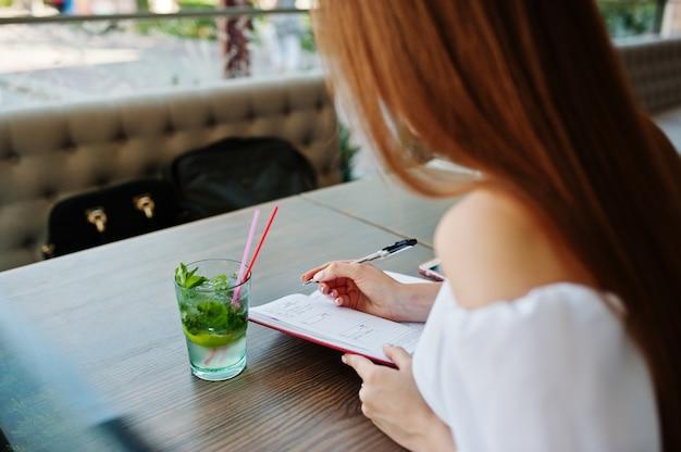 Porträt einer herrlichen erfolgreichen jungen geschäftsfrau, die etwas in ihrem roten notizbuch beim sitzen in einem café notiert.