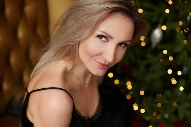 Porträt einer herrlichen frau mit blonden haaren und festlichen weihnachtslichtern