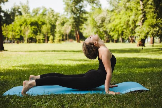 Porträt einer herrlichen jungen frau, die yoga im freien in einem park praktiziert. schönes mädchen in einem schwarzen dünnen anzug.