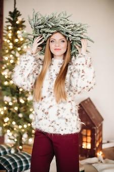 Porträt einer herrlichen jungen frau mit langen haaren, die tannenweihnachtskranz auf kopf tragen und in die kamera lächeln.