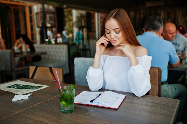 Porträt einer herrlichen jungen geschäftsfrau, die am telefon spricht und etwas in ihrem roten notizbuch beim sitzen in einem café notiert.