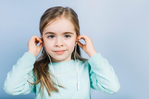 Porträt einer hörenden musik des mädchens auf den kopfhörern, die kamera betrachten