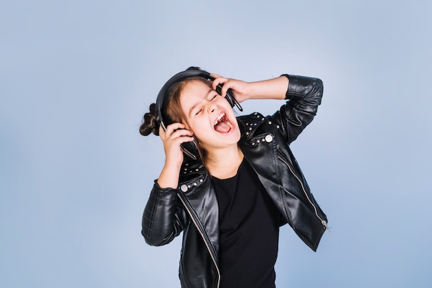 Porträt einer hörenden musik des mädchens auf kopfhörer lachend gegen blauen hintergrund