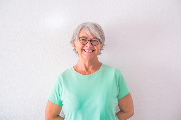 Porträt einer hübschen alten und reifen frau, die lächelnd und lachend in die kamera schaut - glückliche ältere dame mit weißem hintergrund
