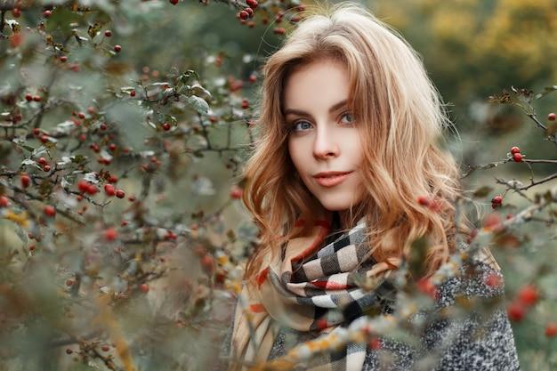 Porträt einer hübschen attraktiven jungen frau mit einem niedlichen lächeln in einem modischen mantel mit einem stilvollen schal draußen nahe einem herbstbaum
