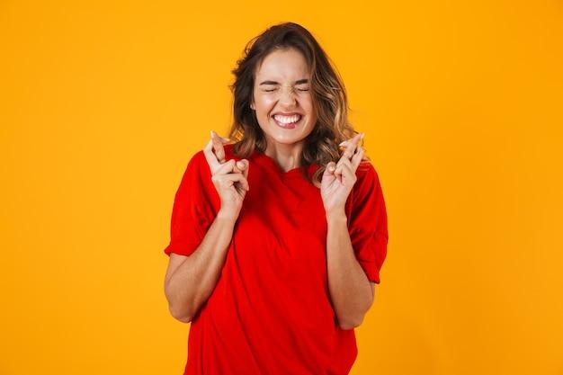 Porträt einer hübschen besorgten jungen frau, die isoliert über gelber wand steht und die daumen für viel glück hält
