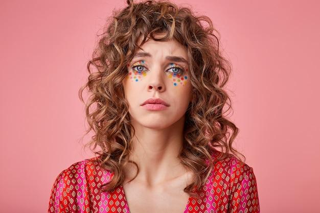 Porträt einer hübschen blauäugigen lockigen jungen frau, die traurig und unglücklich aussieht und verzweifelt weinen wird