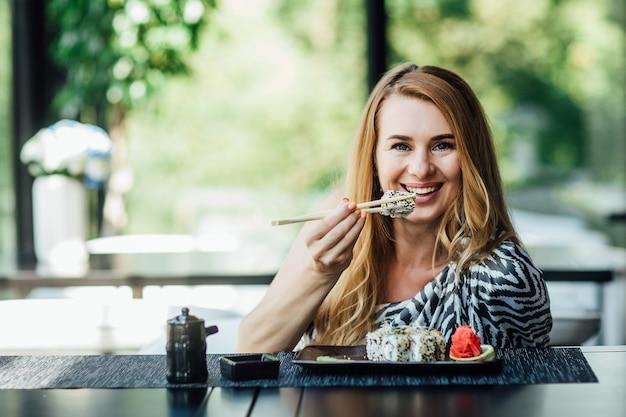 Porträt einer hübschen blonden dame sitzt nach ihrem job im café auf der sommerterrasse mit sushi-rollen.
