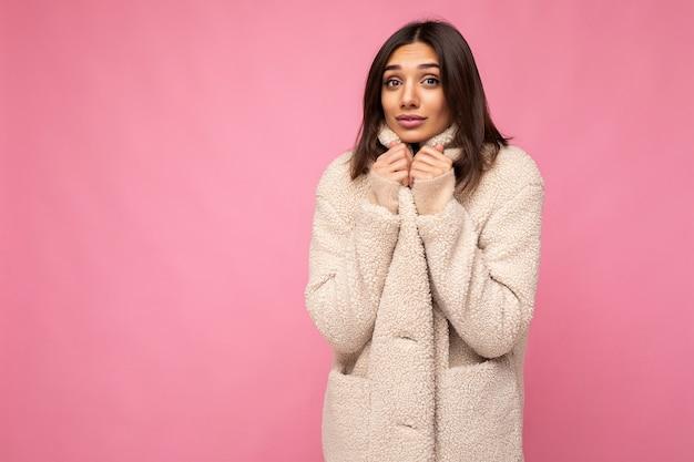 Porträt einer hübschen, charmanten, selbstbewussten, gut aussehenden, stilvollen jungen brünetten frau, die einen warmen herbstmantel trägt, einzeln auf rosafarbenem hintergrund mit kopienraum und sich kalt anfühlt