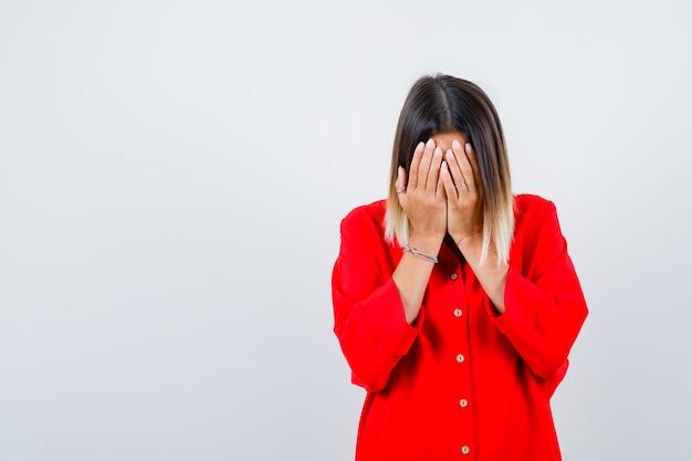 Porträt einer hübschen dame, die das gesicht mit den händen in der roten bluse bedeckt und eine depressive vorderansicht sieht