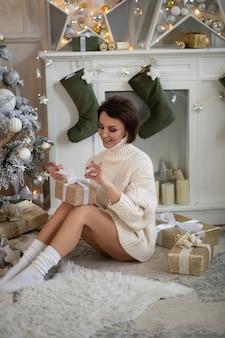 Porträt einer hübschen erwachsenen frau im weißen strickpullover, der weihnachtsgeschenk öffnet, das auf boden sitzt.
