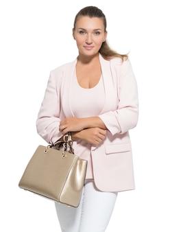 Porträt einer hübschen erwachsenen frau mit handtasche, die im studio aufwirft