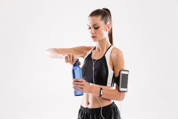 Porträt einer hübschen fitnessfrau in den kopfhörern stehend