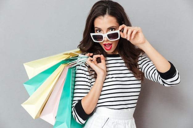 Porträt einer hübschen flirty frau, die einkaufstaschen hält