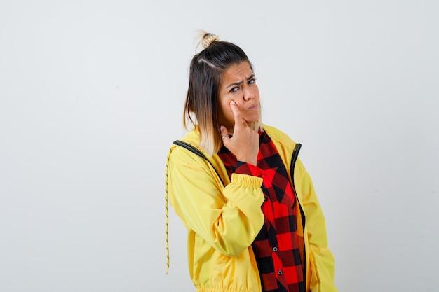 Porträt einer hübschen frau, die auf ihr augenlid in hemd, jacke zeigt und traurige vorderansicht schaut