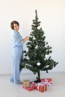 Porträt einer hübschen frau, die den weihnachtsbaum schmückt.