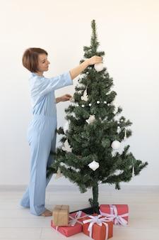 Porträt einer hübschen frau, die den weihnachtsbaum schmückt