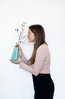 Porträt einer hübschen frau, die eine pflanze riecht