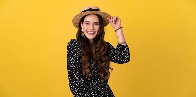 Porträt einer hübschen frau, die isoliert auf gelb posiert und ein schwarzes gepunktetes kleid und einen stilvollen boho-trend mit strohhut trägt