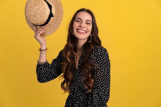 Porträt einer hübschen frau, die isoliert auf gelb posiert und ein schwarzes gepunktetes kleid und einen strohhut trägt
