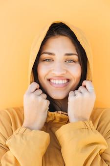 Porträt einer hübschen frau, die kamera mit hoodiejacke betrachtet