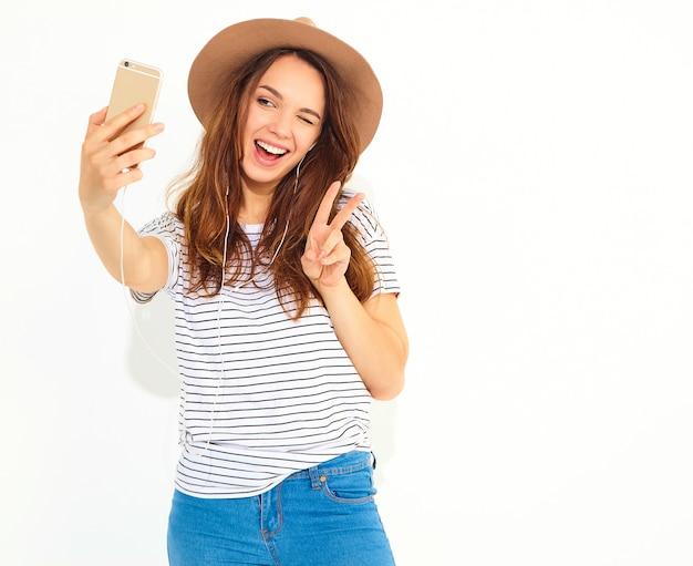 Porträt einer hübschen frau im sommerhippie kleidet das nehmen eines selfie, das auf weißer wand lokalisiert wird. friedenszeichen blinzeln und zeigend