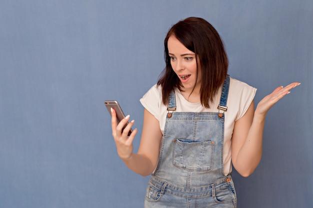 Porträt einer hübschen frau mit einem telefon in den händen. unterschiedliche gefühle eines mädchens.