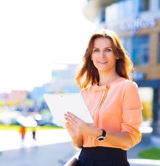 Porträt einer hübschen geschäftsfrau in smart casual mit digitalem tablet im freien