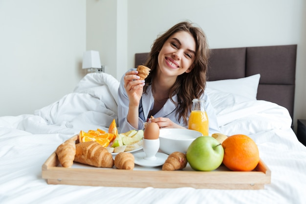 Porträt einer hübschen glücklichen frau, die im bett frühstückt