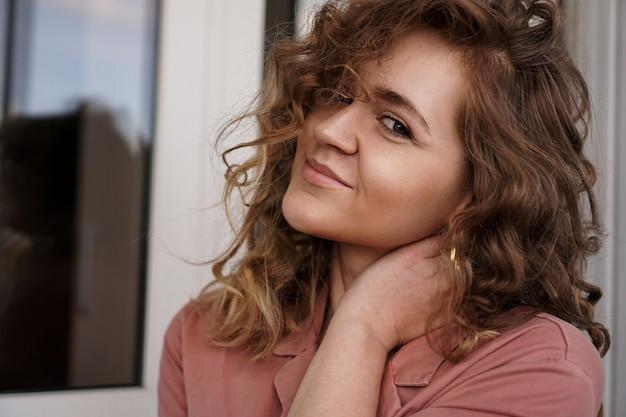 Porträt einer hübschen glücklichen frau mit lockigem haar