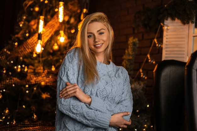 Porträt einer hübschen glücklichen jungen frau mit einem niedlichen lächeln in einem trendigen strickanzug auf dem hintergrund eines festlichen weihnachtsbaumes mit weinlesegirlanden