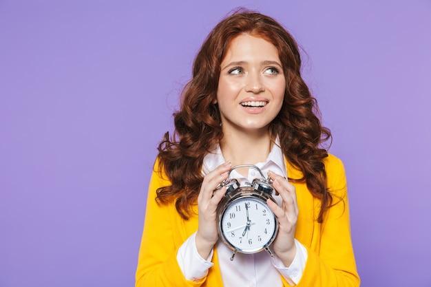 Porträt einer hübschen glücklichen jungen rothaarigen frau, die über veilchen steht und wecker zeigt