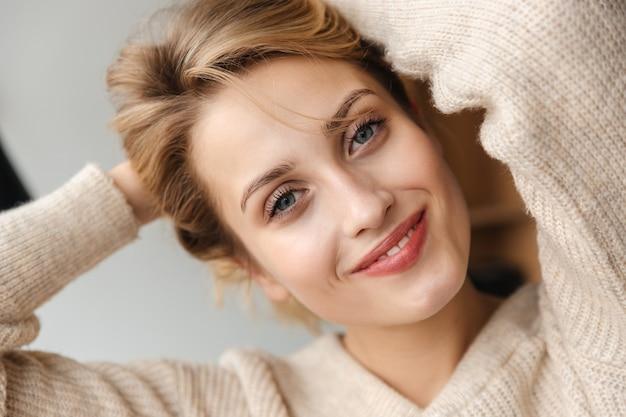 Porträt einer hübschen glücklichen lächelnden optimistischen jungen frau, die zuhause zu hause aufwirft.