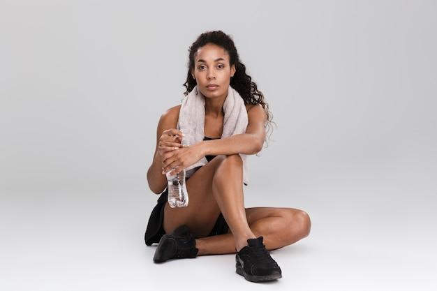 Porträt einer hübschen jungen afrikanischen sportlerin, die nach dem training isoliert über grauer wand, trinkwasser ruht