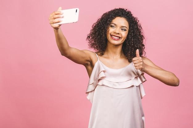 Porträt einer hübschen jungen afro-amerikanerin im kleid beim stehen und nehmen eines selfies lokalisiert über rosa hintergrund.