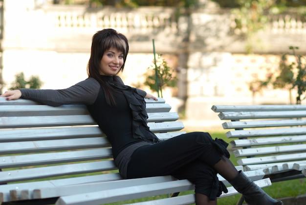 Porträt einer hübschen jungen frau, die auf einer bank im park sitzt?