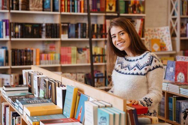 Porträt einer hübschen jungen frau, die bücher in der bibliothek wählt