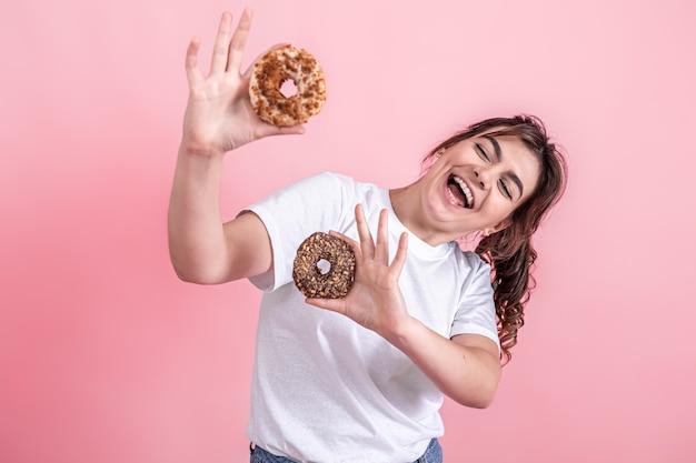 Porträt einer hübschen jungen frau, die donuts auf rosafarbenem hintergrund isoliert zeigt