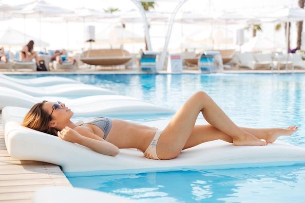 Porträt einer hübschen jungen frau, die draußen auf dem liegestuhl am swimmingpool liegt