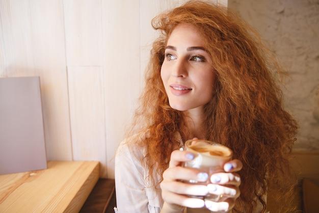 Porträt einer hübschen jungen frau, die ihr kaffeegetränk riecht