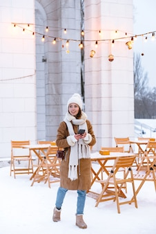 Porträt einer hübschen jungen frau in der mütze und im schal, die draußen im winterschnee gehen, der kaffee mit handy trinkt.