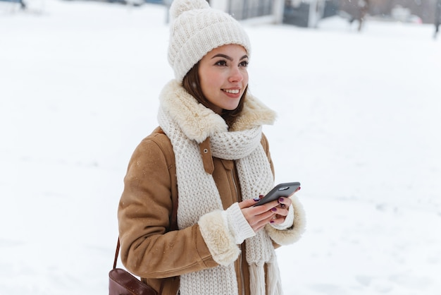 Porträt einer hübschen jungen frau in der mütze und im schal, die draußen im winterschnee unter verwendung des mobiltelefons gehen.