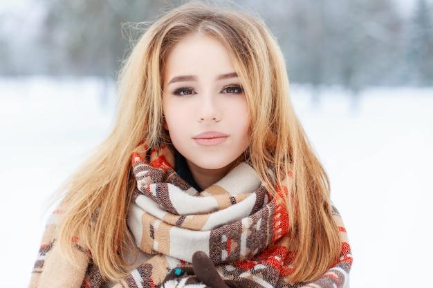 Porträt einer hübschen jungen frau mit braunen augen mit schönem make-up mit langen blonden haaren in einem warmen wollschal in einem schneebedeckten park. süßes mädchen auf einem spaziergang.