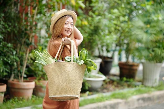 Porträt einer hübschen jungen frau mit strohhut, die eine einkaufstasche mit lebensmitteln trägt, sich umdreht und in die kamera schaut