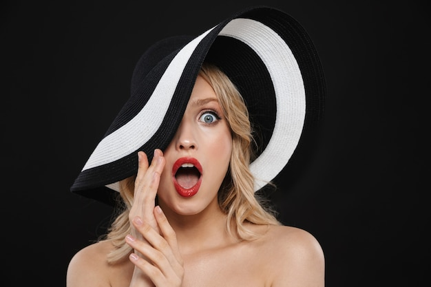 Porträt einer hübschen jungen schockierten blonden frau mit den roten lippen des hellen make-ups, die isolierten tragenden hut aufwerfen.
